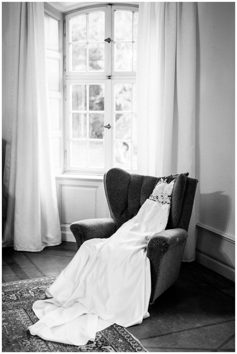 Das Brautkleid liegt am Hochzeitstag bereit auf einem Sessel.