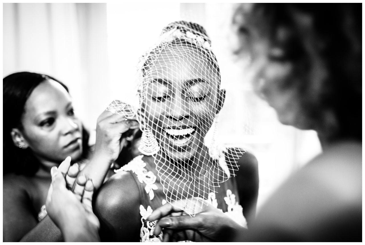 Die Braut lacht beim Getting Ready, während die Trauzeugin ihr Ohrringe ansteckt.