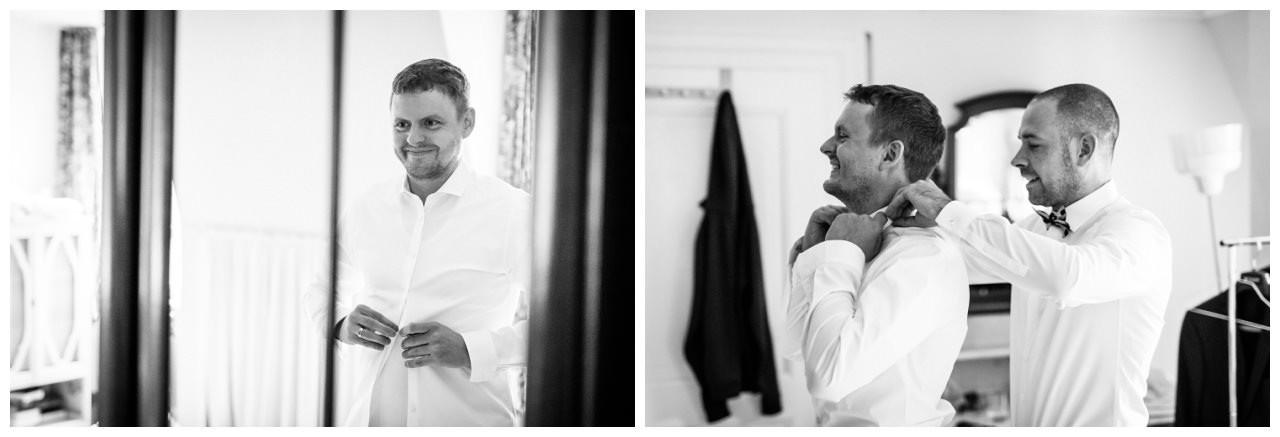 Der Bräutigam zieht sein Hemd an.
