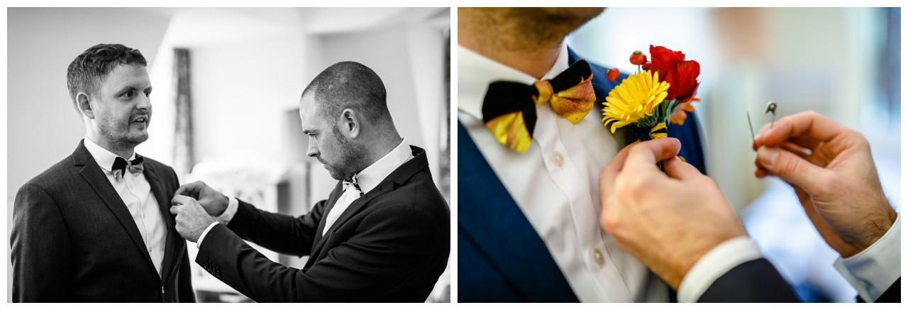 Der Trauzeuge hilft dem Bräutigam beim Anziehen.