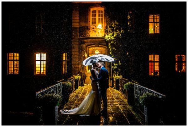 Das Brautpaar steht unter einem Schirm im Regen. Hochzeitsfoto im Regenh.