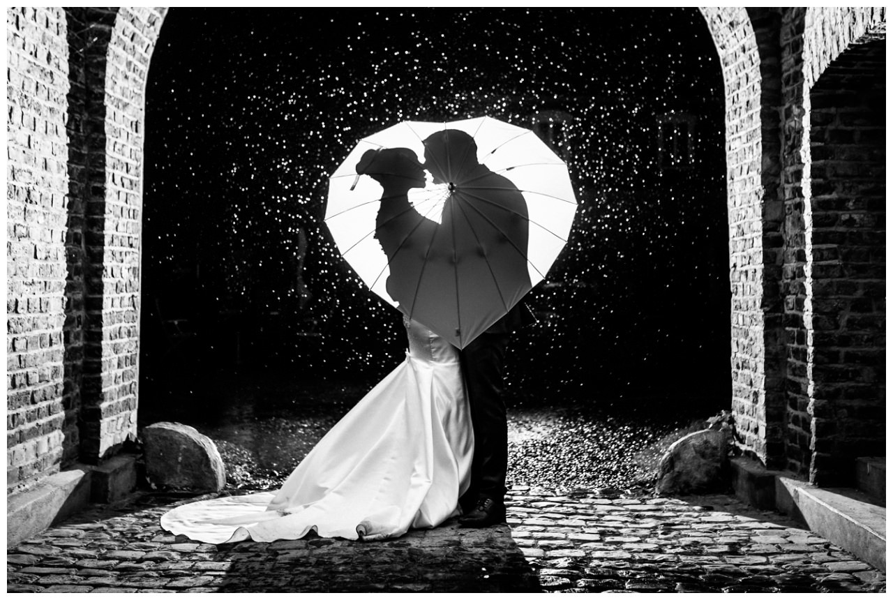 Hochzeitsfoto im Regen, das Brautpaar steht unter einem Schirm.