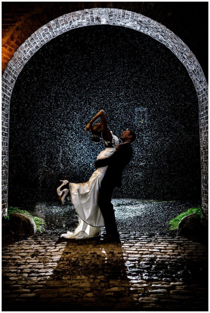 Hochzeitsfoto im Regen, die Braut wird vom Bräutigam in die Luftt gehoben.