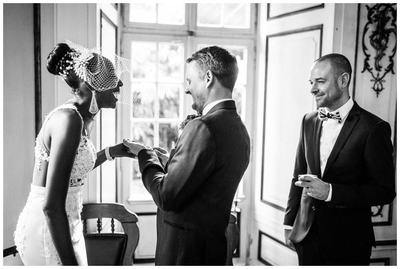 Der Bräutigam steckt der Braut den Ring an.
