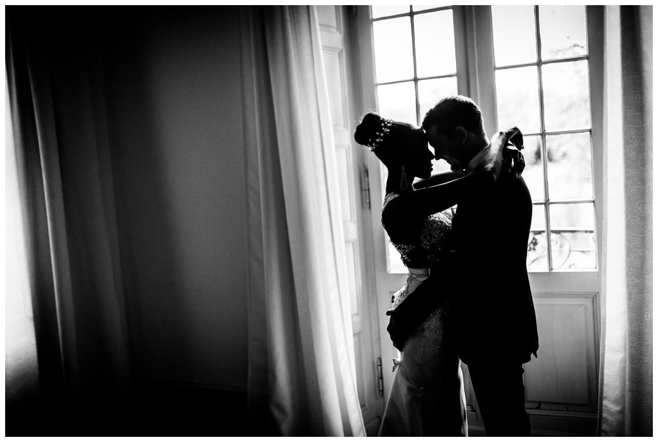Die Siljouette des Brautpaares ist zu sehen, das Brautpaar umarmt sich.