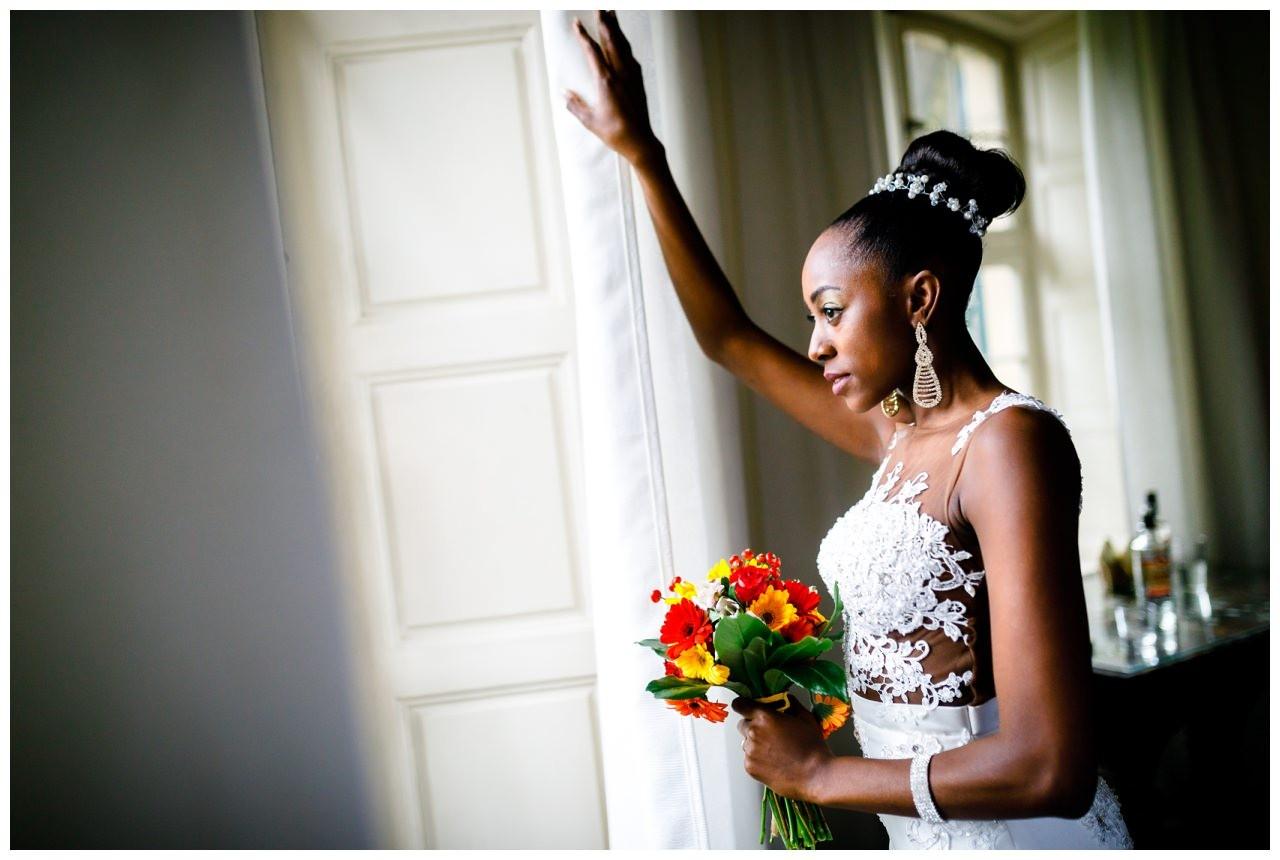 Die Braut sieht verträumt aus dem Fenster.