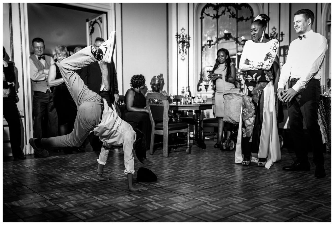 Der Trauzeuge tanzt breakdance, das Brautpaar guckt zu.