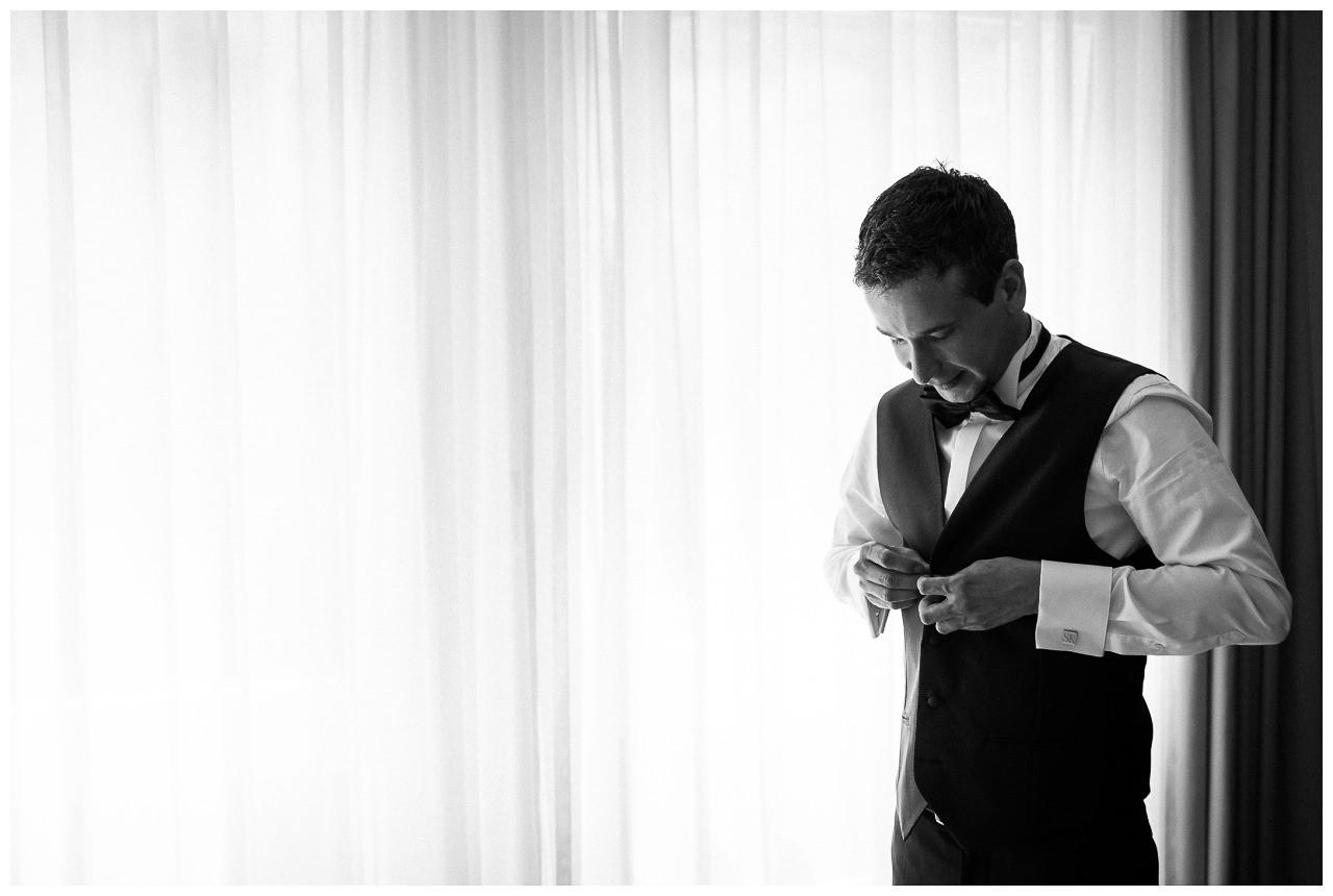 Beim Gettingready knöpft sich der Bräutigam seine Weste zu.