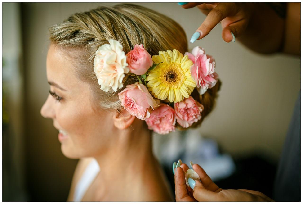 Brautfrisur mit vielen frischen Blumen im Haar.