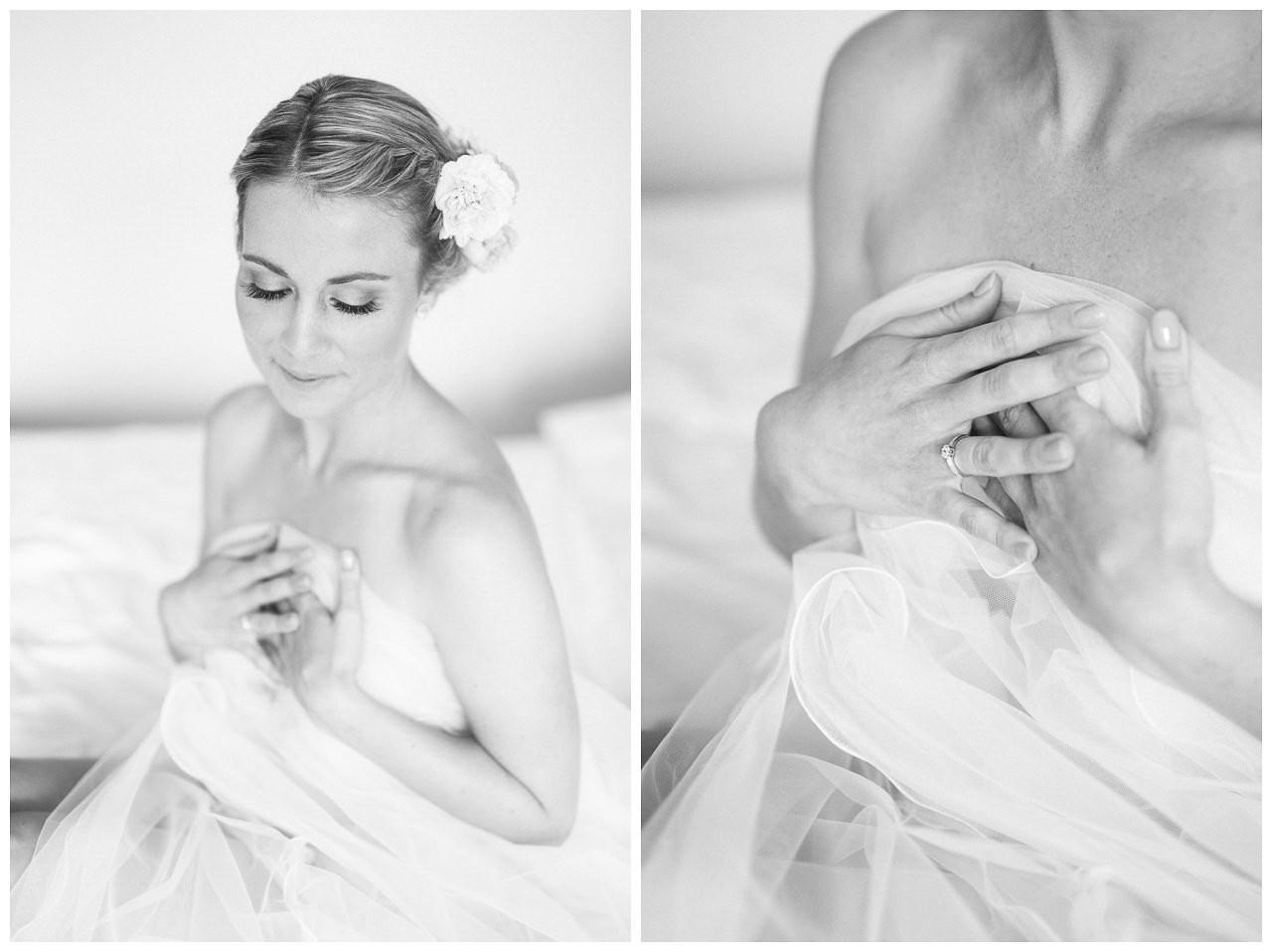 Budoir-Aufnahme der Braut; die Braut sitzt auf dem Bett und wickelt sich in ein Bettlacken,