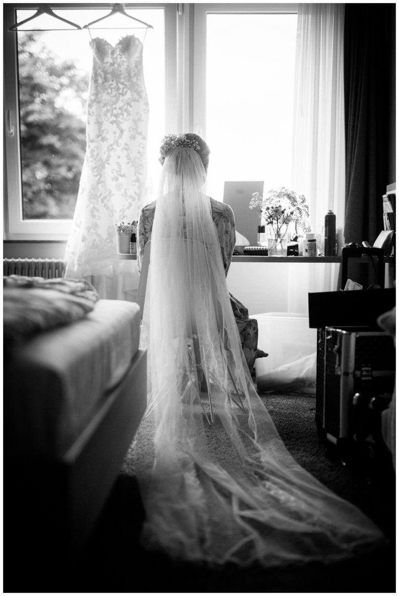 Getting Ready der Braut, die Braut mit Schleier ist von hinten zu sehen, im Hintergrund hängt ihr Kleid.