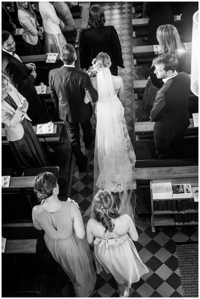 Der Mittelgang der Kirche beid er Hochzeit; die Braut wird von ihrem Brautvater geführt.
