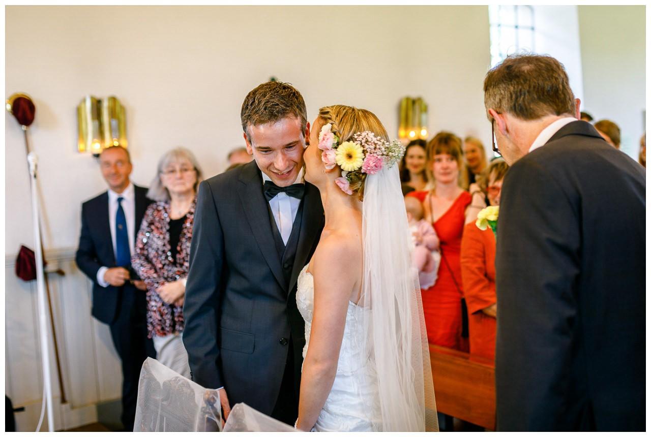 Die Braut gibt dem Bräutigam bei der kirchlichen Trauung vor dem Altar ein Küsschen auf die Wange.