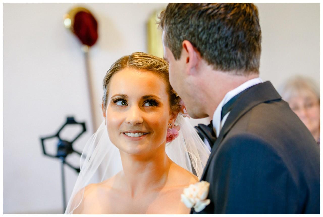 Kirchliche Trauung, die Braut strahlt vor dem Altar ihren Bräutigam an.