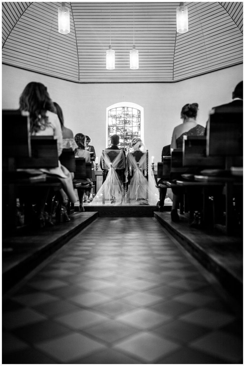Kirchliche Trauung, das Brautpaar sitzt vor dem Altar.