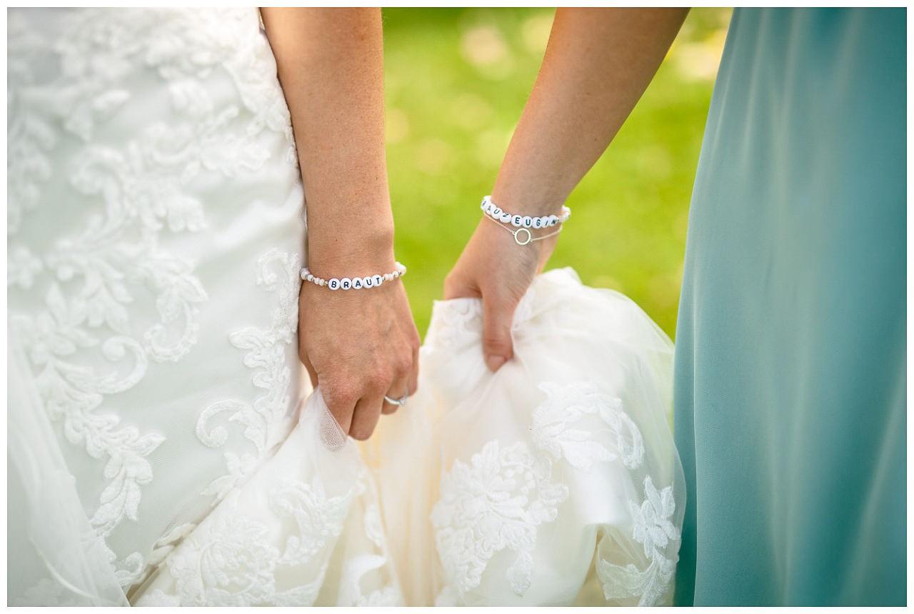 Geschenk für die Trauzeigin; Braut und Trauzeugin tragen Perlenarmbänder.