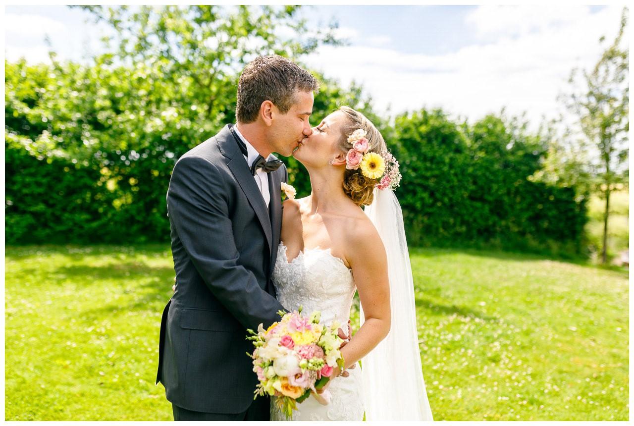 Brautpaar-Shooting, dasd Brautpaar küsst sich auf einer Wiese.