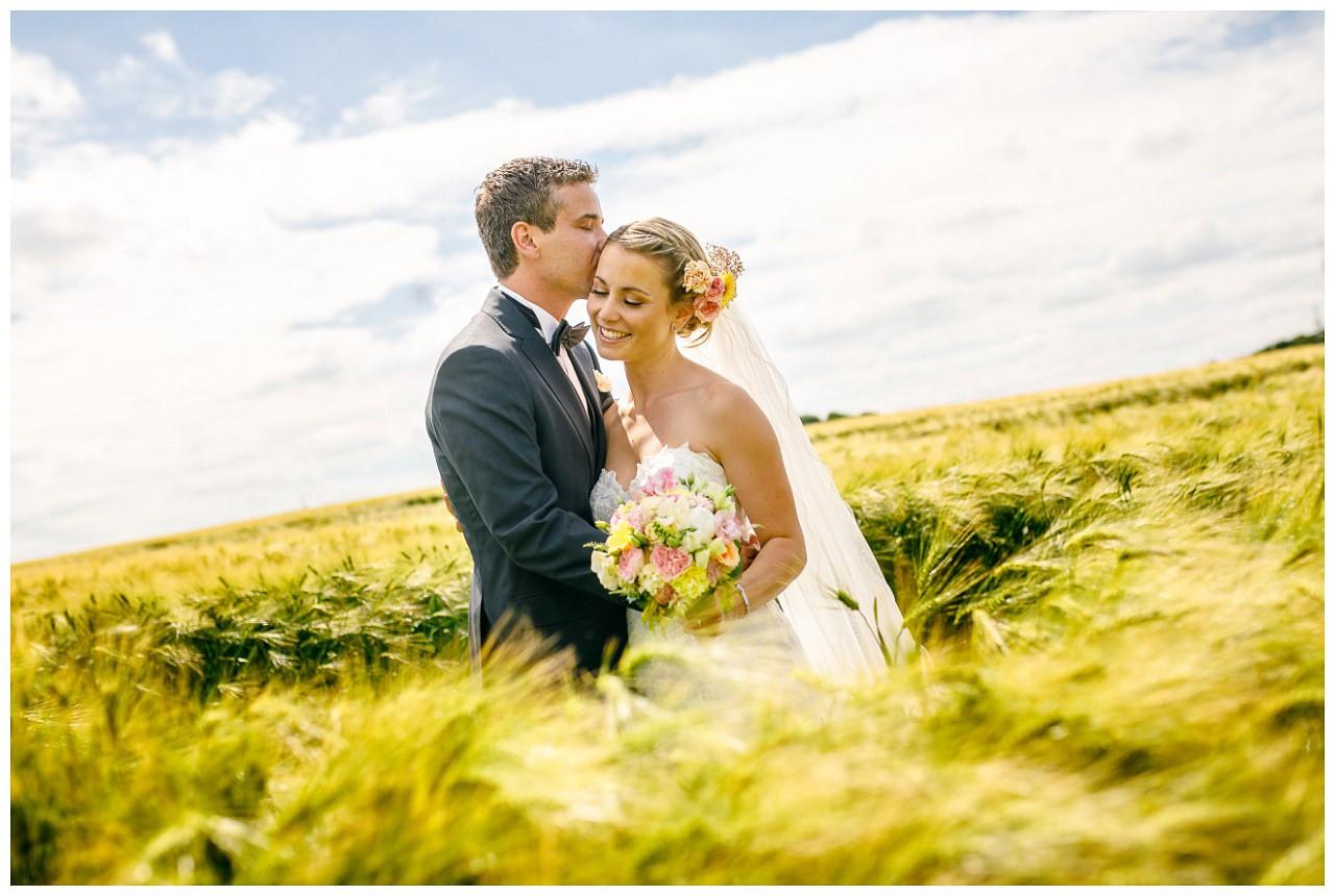 Brautpaar-Shooting; das Brautpaar steht auf einem Kornfeld.