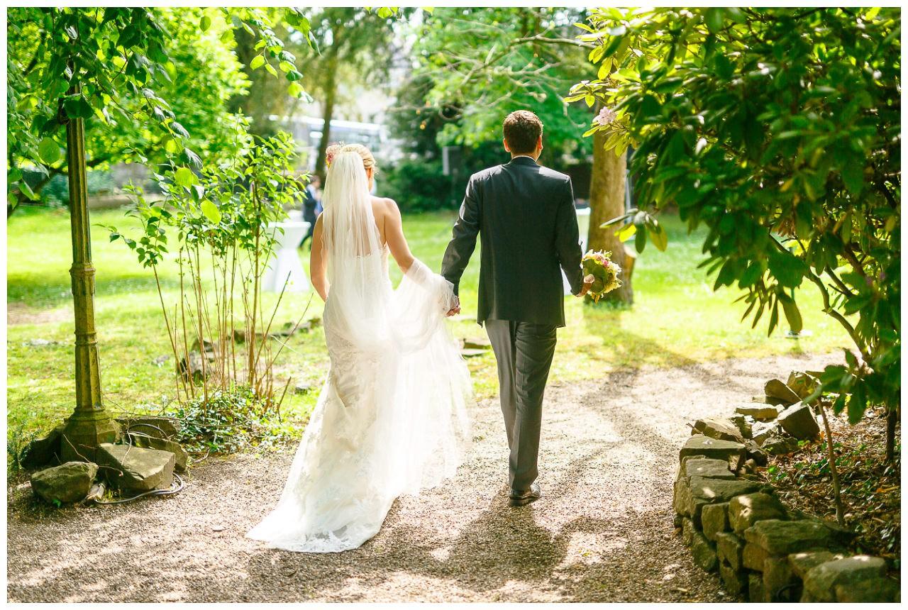 Hochzeit, das Brautpaar läuft einen Weg entlang.