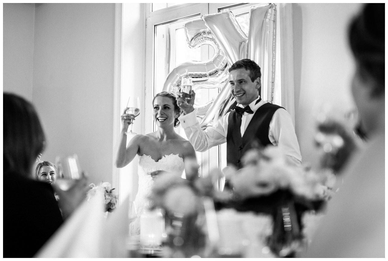 Hochzeitsfeier: das Brautpaar spricht einen Tost aus.