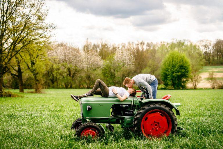 Die Schwangere liegt auf einem Traktor, ihr Mann küsst sie.