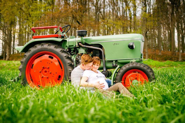 Schwangerschaftsfoto vor einem alten Traktor.