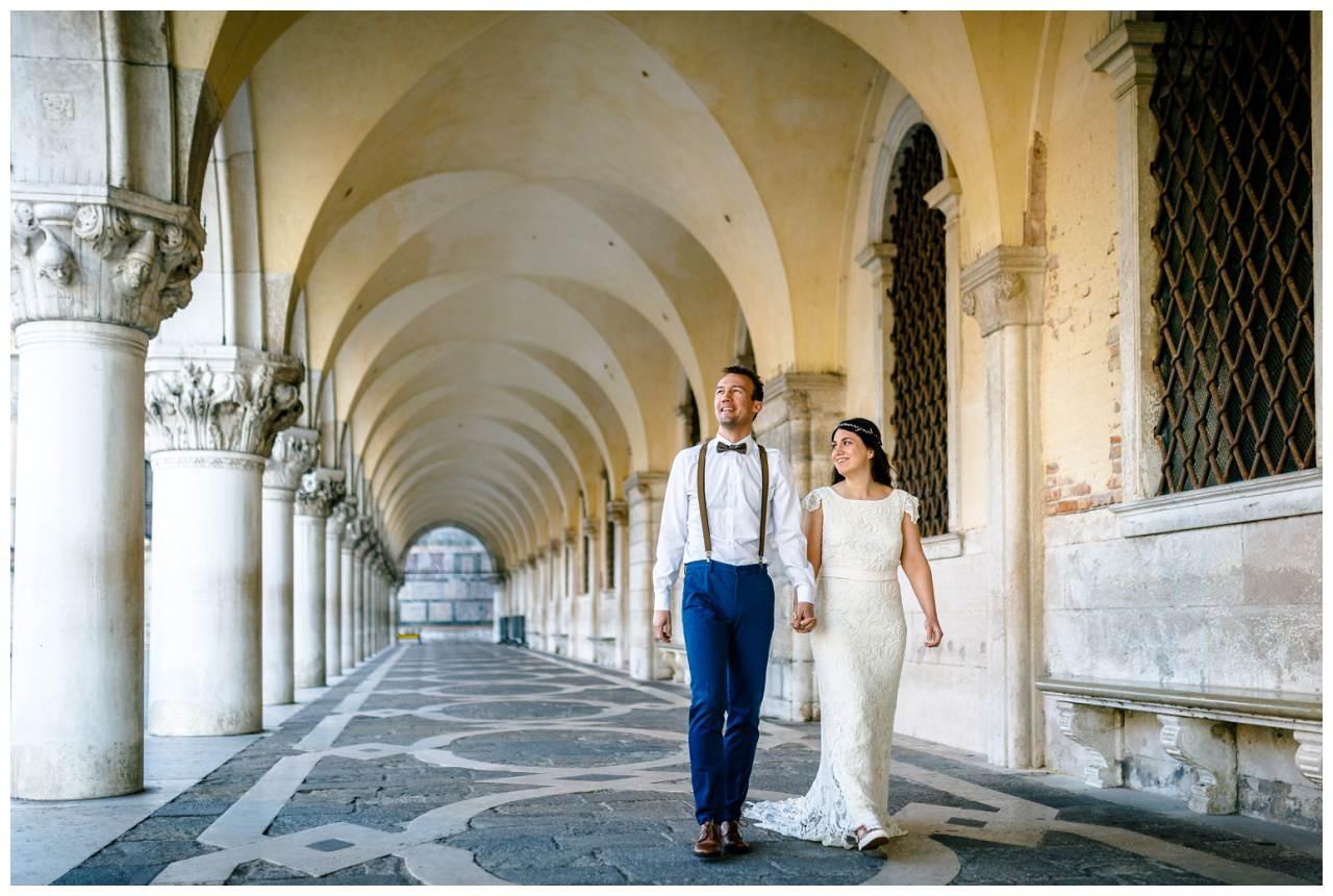 After Wedding Shooting in Venedig das Brautpaar läuft einen Säulengang am Marcusplatz entlang