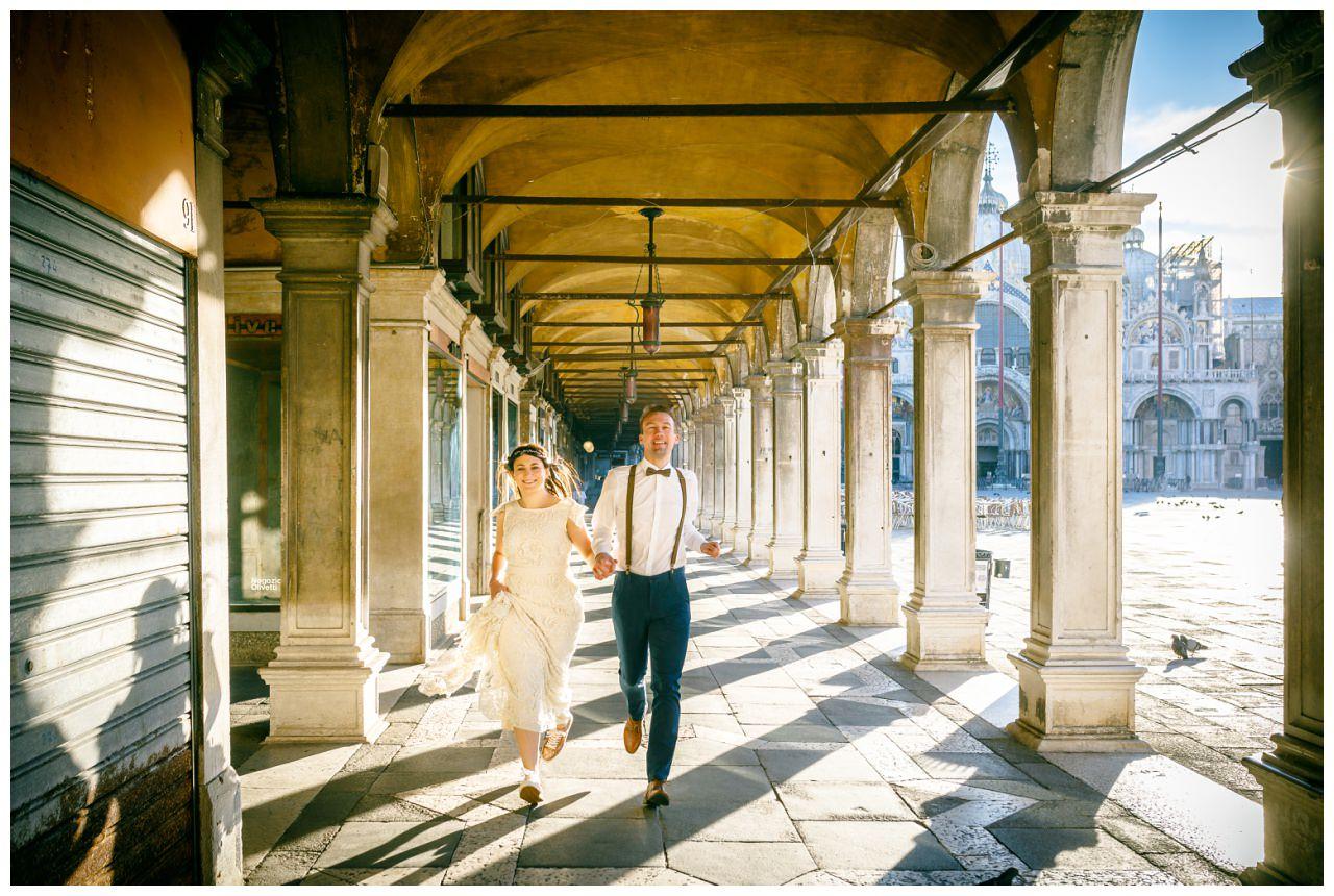 After Wedding Shooting in Venedig das Brautpaar rennt am Marcusplatz durch einen Säulengang