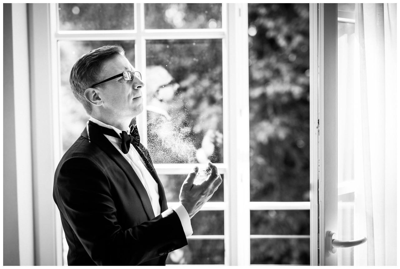Hochzeitsfotos in der Wipperaue Solingen der Bräutigam besprüht sich mit seinem Duft zur Hochzeit