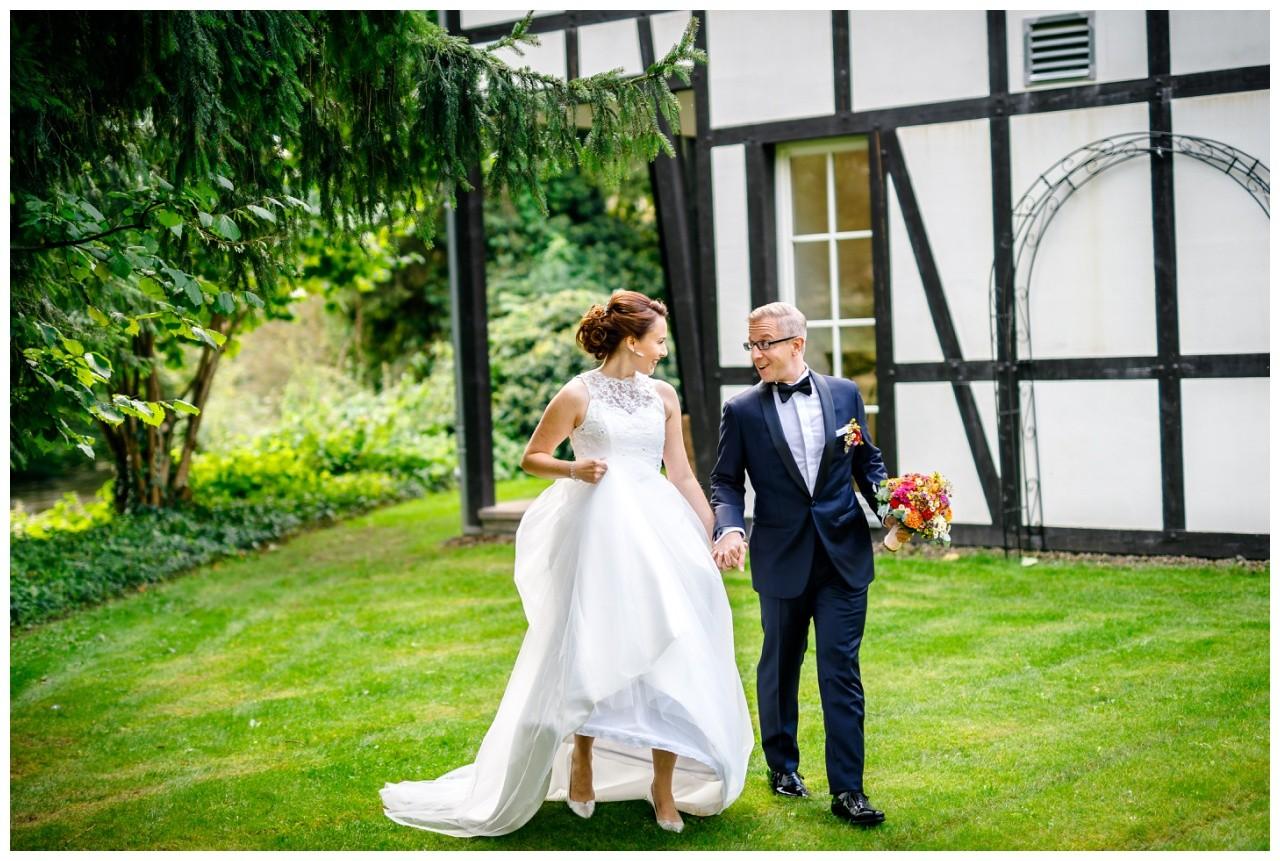 Das Brautpaar geht Hand in Hand zur freien Trauung in der Wipper Aue in Solingen