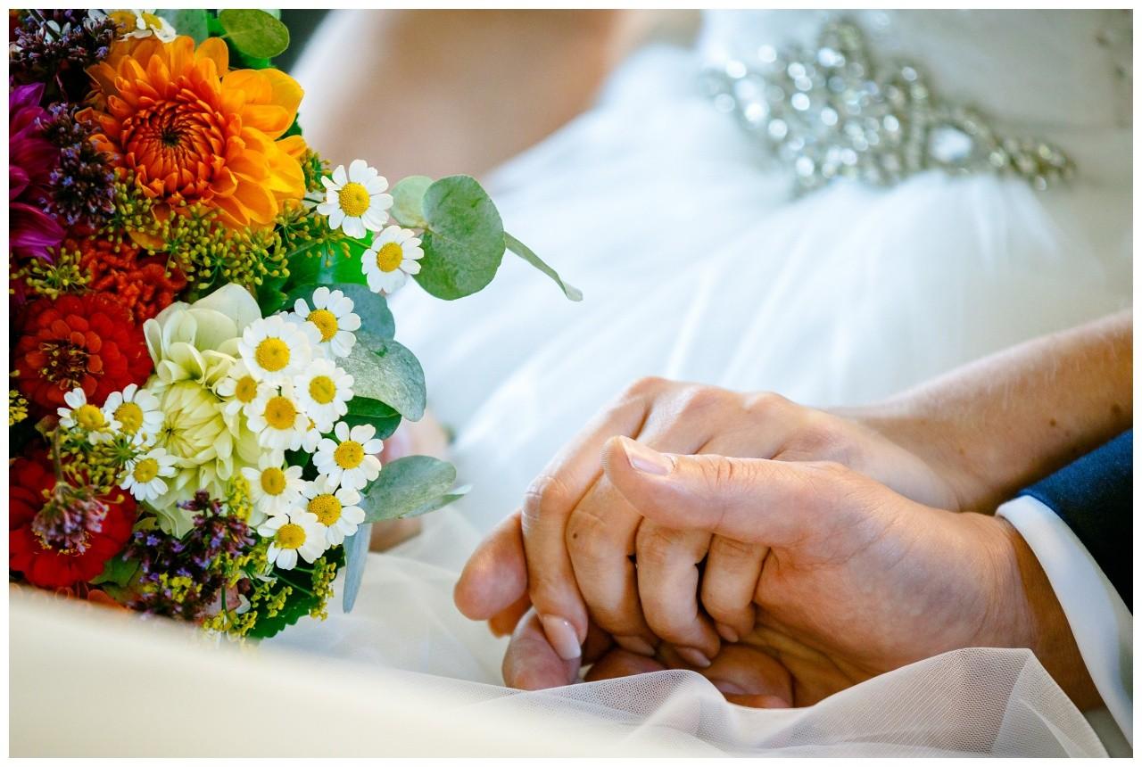 Das Brautpaar hält Händchen bei der Hochzeit in der Wipper Aue in Solingen