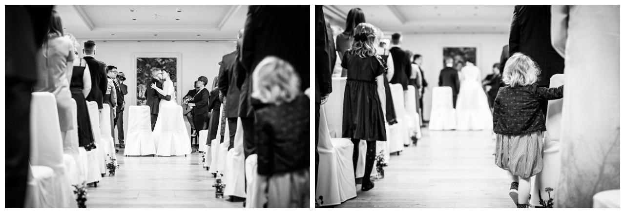 Ein kleines Mädchen sieht zu wie sich das Brautpaar küsst bei der Hochzeit in Solingen