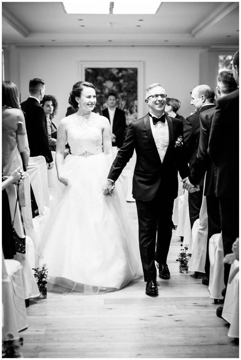 Das Brautpaar geht nach der freien Trauung den Mittelgang zwischen den Gästen entlang