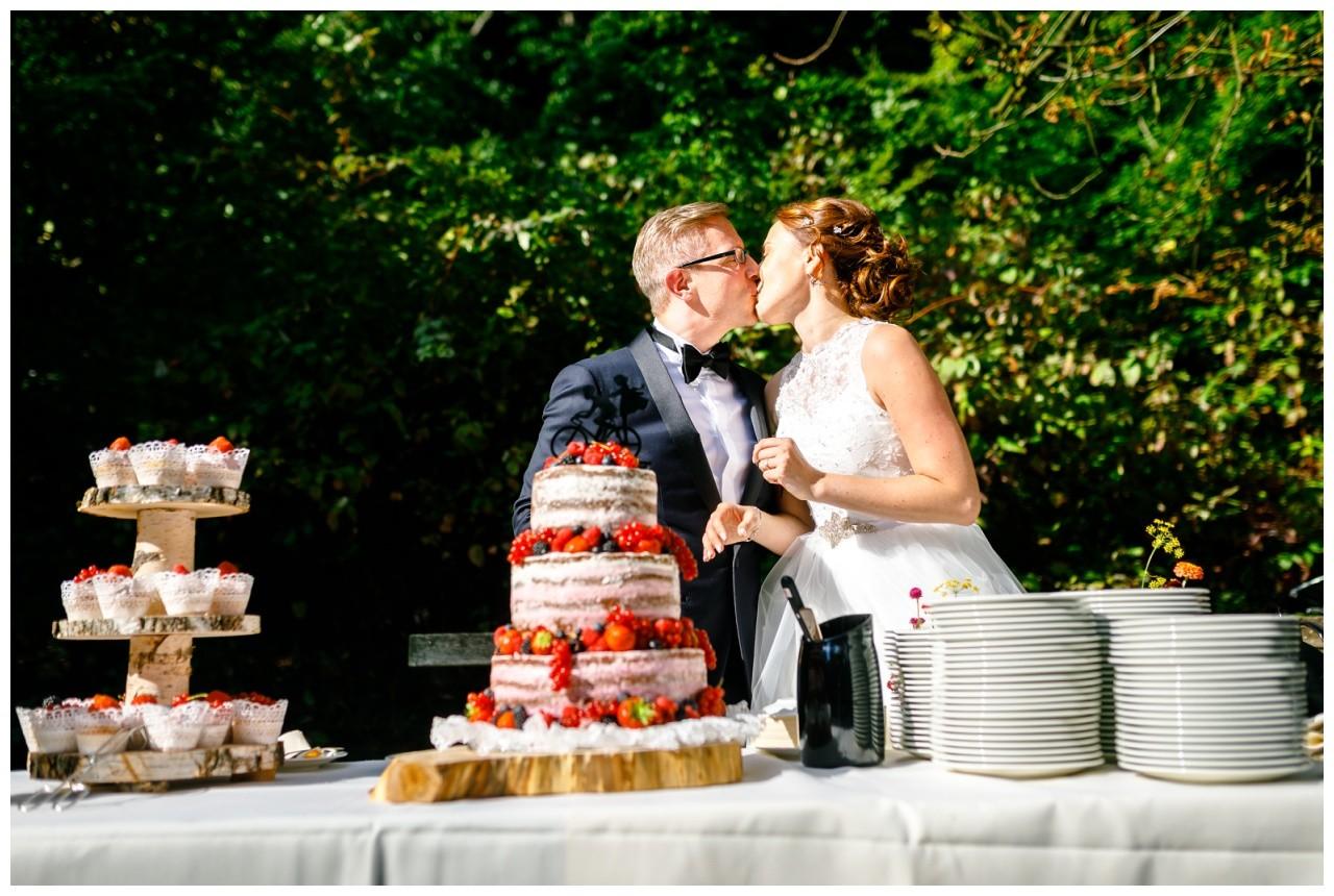 Das Brautpaar gibt sich nach dem Anschnitt der Hochzeitstorte einen Kuss