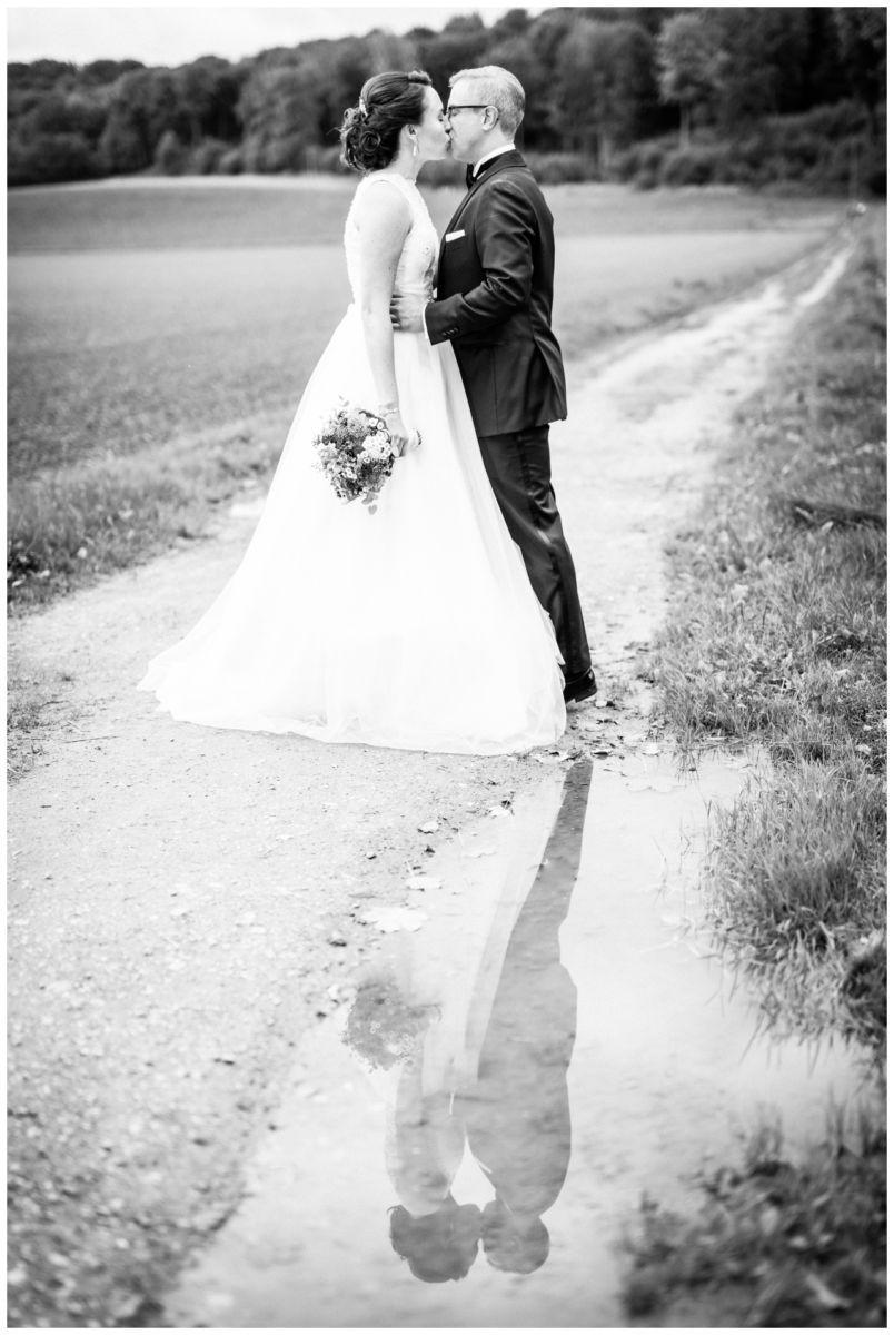 Das Brautpaar spiegelt sich in einer Pfütze