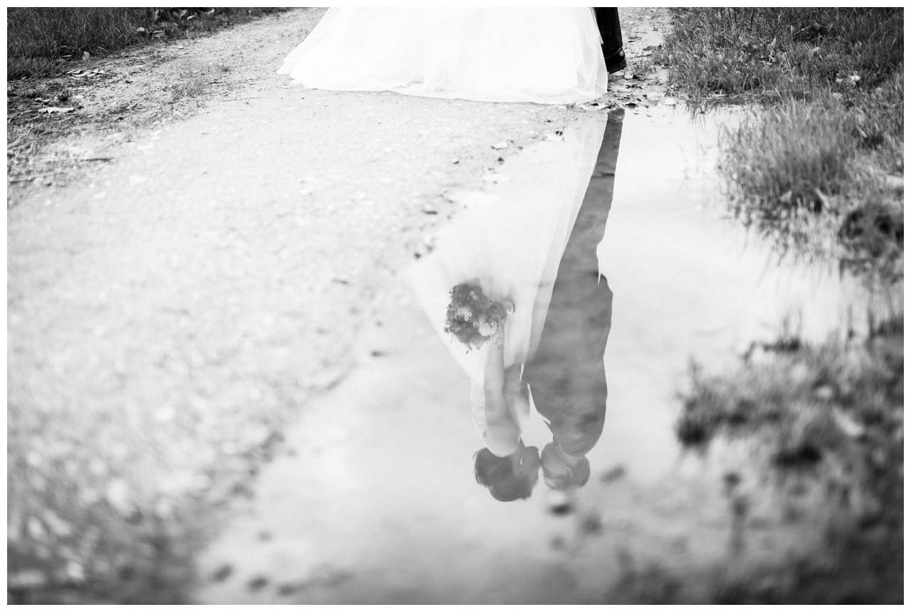 Spiegelung des Brautpaares in einer Pfütze bei der Hochzeit in Solingen