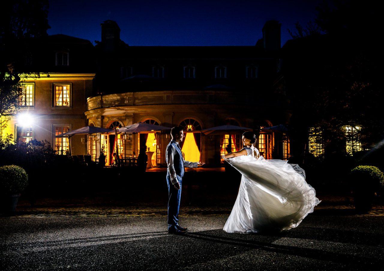 Hochzeitsfoto im Dunkeln, das Brautpaar tanzt in der Nacht vor ihrer Hochzeitslocation.
