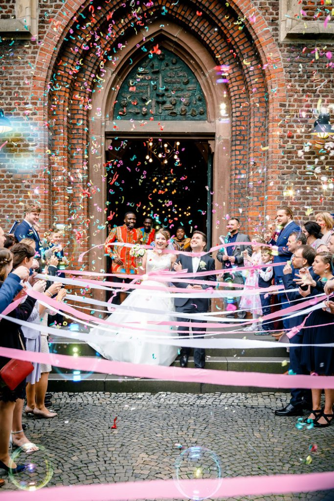 Hochzeitsfoto vor der Kirche, das Brautpaar kommt aus der Kirche und wird mit Konfetti und Seifenblasen empfangen.