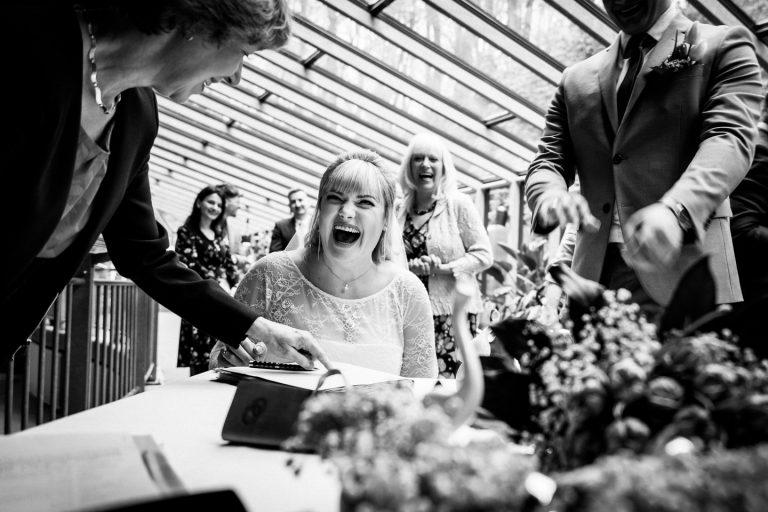 Die Braut sitzt im Standesamt und unterschreibt die Heiratsurkunde. Die Braut lacht.