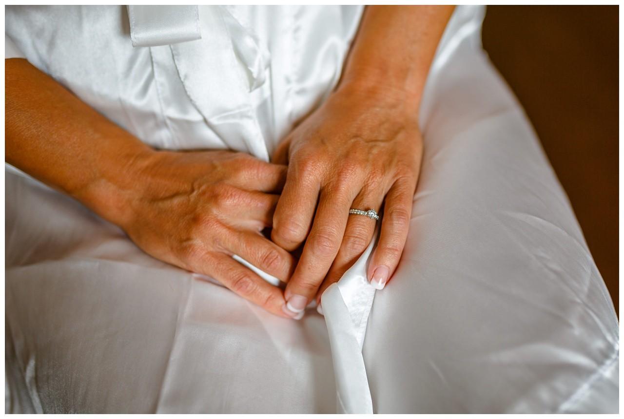 Die Hände der Braut mit Verlobungsring