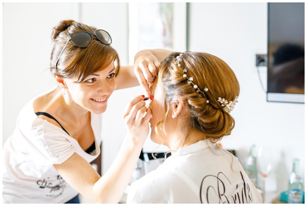 Die Visagistin schmink die Braut für die Hochzeit auf dem Chiemsee