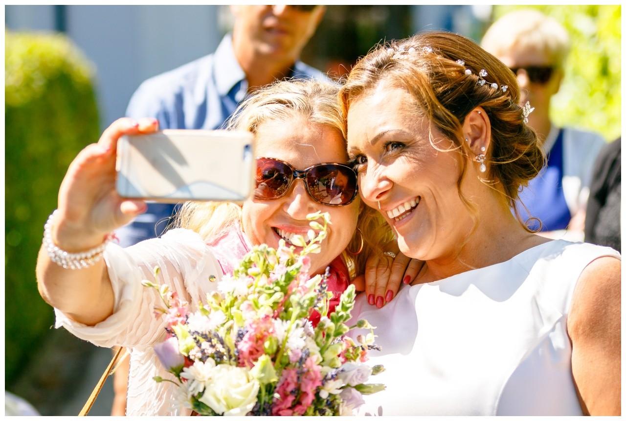Trauzeugin und Braut machen ein Selfie bei der Hochzeit am Chiemsee