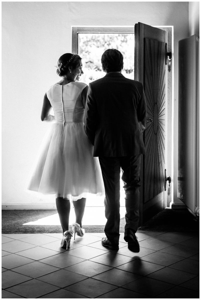 Das Brautpaar geht nebeneinander aus dem Standesamt auf der Fraueninsel Chiemsee