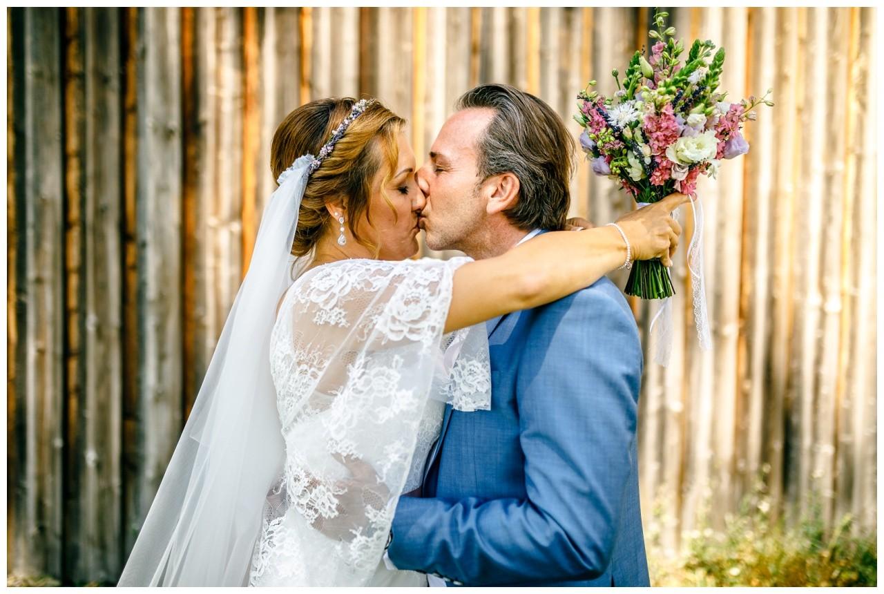 Hochzeitsfotograf Chiemsee das Brautpaar küsst sich auf der Fraueninsel