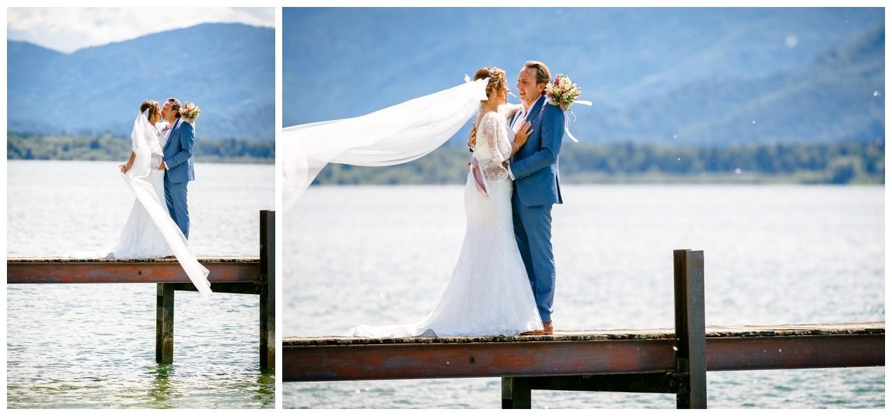 Hochzeitsfotos auf dem Chiemsee das Brautpaar steht auf dem Steg auf dem Chiemsee, der Schleier weht