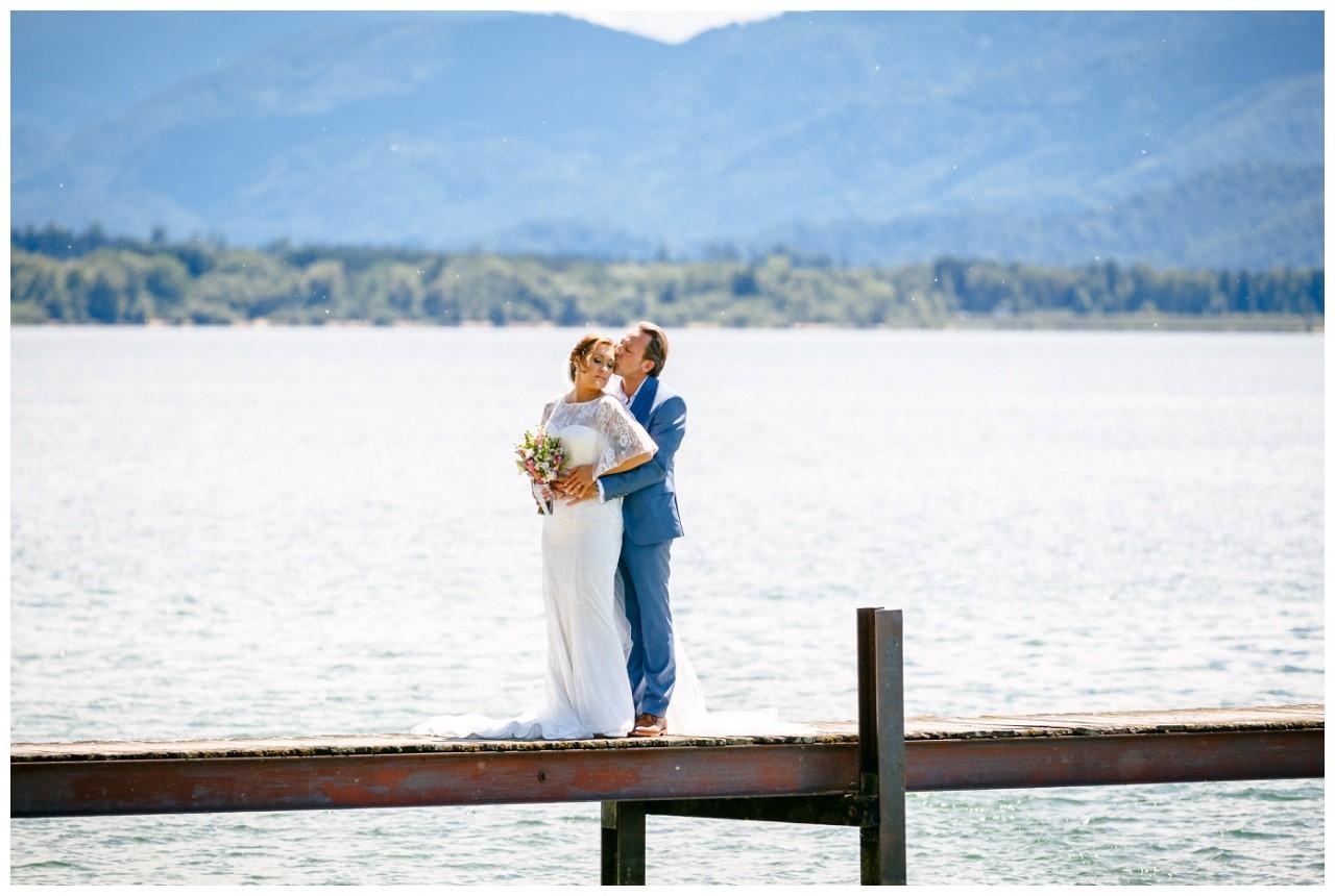 Hochzeitsshooting auf dem Chiemsee, das Brautpaar steht auf einem Steg