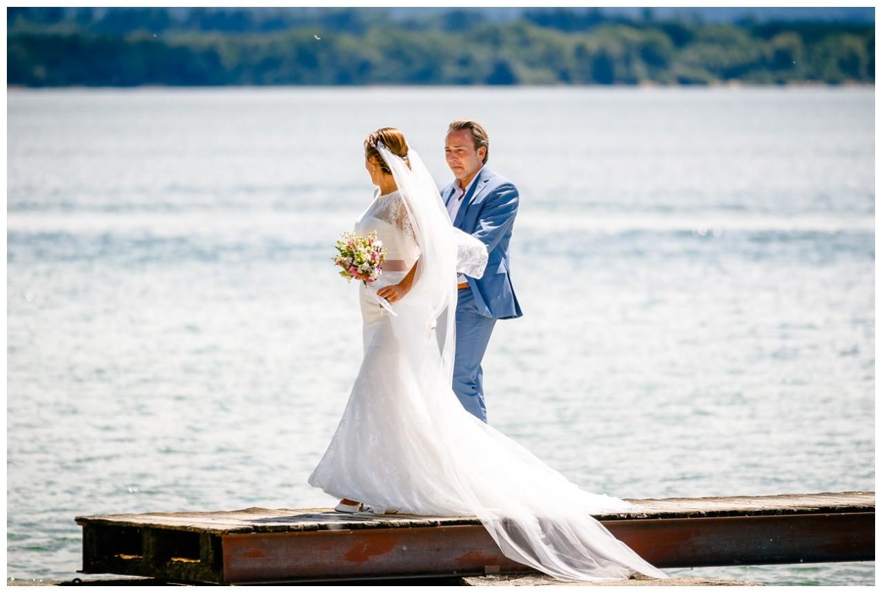 Hochzeitsfotos Chiemsee das Brautpaar läuft auf einem Steg