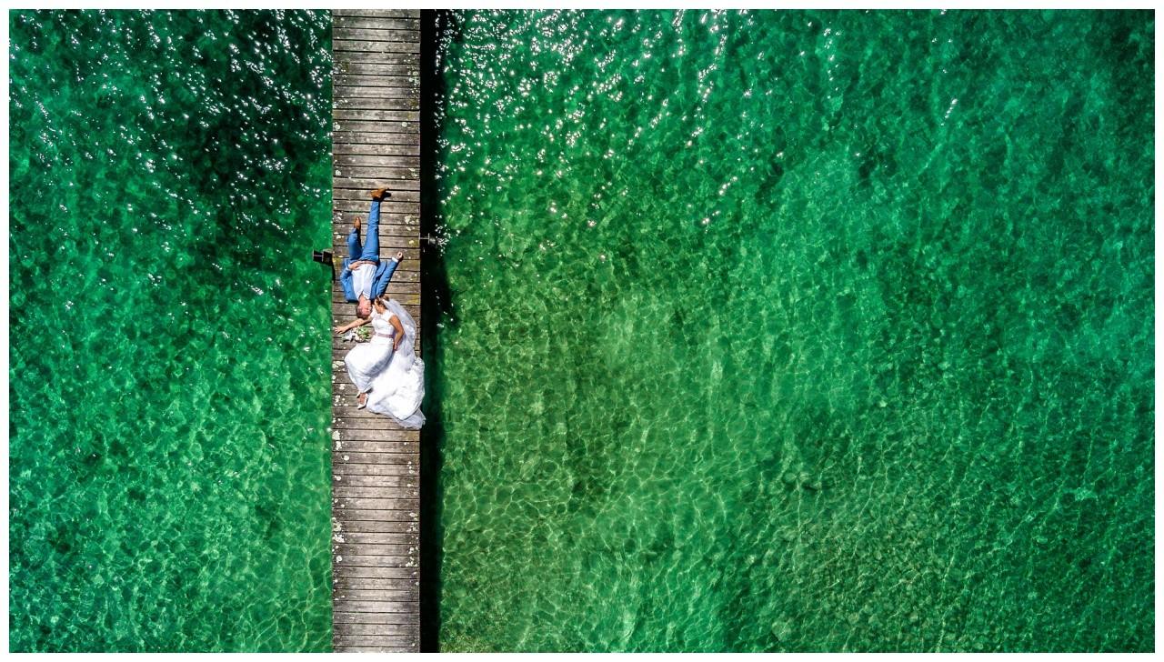 Hochzeitsfoto auf dem Chiemsee, das Brautpaar liegt auf einem Steg und wird von oben fotografiert