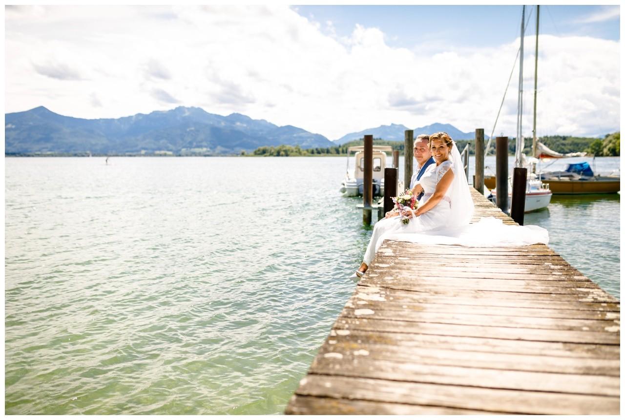 Hochzeitsfotograf Chiemsee, das Brautpaar sitzt auf einem Steg