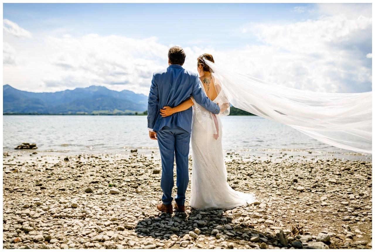 Hochzeitsshooting am Chiemsee, das Brautpaar ist von hinten zu sehen und der Schleier weht im Wind